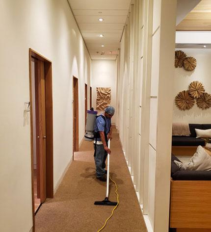 man vacuuming an apartment building hallway